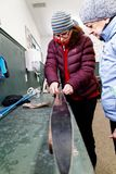 A woman showing someone how to prepare cross country skis royalty free stock image