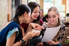 Young woman showing paperwork to her friends. Young women showing paperwork to her friends while sitting together in a coffee shop Stock Photography
