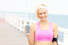 Young woman showing phone over pier Stock Photos
