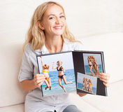 Young woman showing photo book Stock Photos