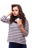 Young woman showing a pill with severe head pain with tablets Royalty Free Stock Photos