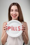 Young woman showing plate with pills Royalty Free Stock Photos