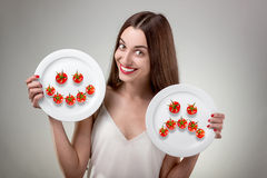 Young woman showing plate. Stock Photos