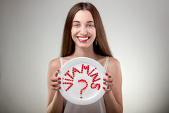 Young woman showing plate with vitamins Stock Image