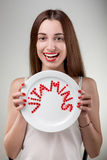 Young woman showing plate with vitamins Royalty Free Stock Photo