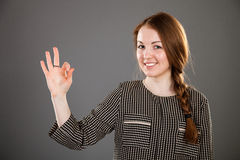 Young woman showing positive gesture. On grey background Stock Image