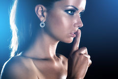 Young woman showing quiet handsign. On dark background Royalty Free Stock Photography