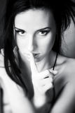 Young woman showing quiet sign. Black and white concept portrait Royalty Free Stock Photo