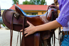 Young woman showing a saddle in her hand Royalty Free Stock Photo