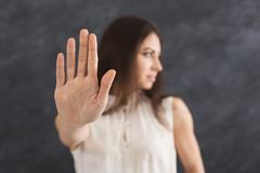Young woman showing sign stop. Young woman saying no. Girl denying proposal, making stop gesture with her hand. Studio shot, copy space stock photography