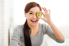 Young woman showing slices of kiwi fruit Stock Image