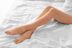 Young woman showing smooth silky skin after epilation. On bed at home Stock Photos