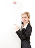 Young woman showing something on blank poster Royalty Free Stock Photo