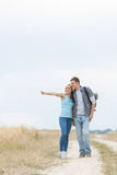 Young woman showing something to man while standing on trail at field. Young women showing something to men while standing on trail at field stock photos