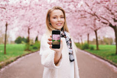 Young woman showing spring park picture on her mobile phone stock photography