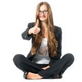 Young woman showing success sitting cross legged Stock Photos
