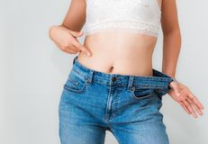 Young woman showing successful weight loss with her jeans, Healt. Young woman showing successful weight loss with her jeans., Healthcare, Diet concept Royalty Free Stock Image