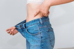 Young woman showing successful weight loss with her jeans., Heal. Thcare, Diet concept Royalty Free Stock Photography