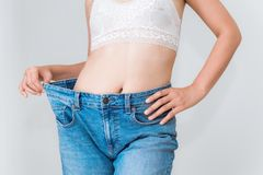 Young woman showing successful weight loss with her jeans, Healt. Young woman showing successful weight loss with her jeans., Healthcare, Diet concept Stock Photography