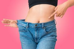 Young woman showing successful weight loss with her jeans on iso. Late background., Healthcare, Diet concept Stock Image