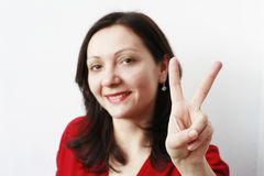 Young woman showing the symbol of peace Royalty Free Stock Image