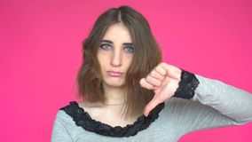 Young woman showing thumb down. Posing against pink background. stock video