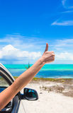 Young woman showing thumbs up on the beach Stock Image