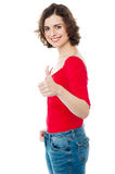 Young woman showing thumbs up gesture Stock Photo