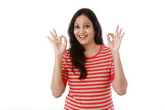 Young woman showing thumbsup gesture against white royalty free stock photography