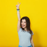 Young woman showing two fingers on yellow background Royalty Free Stock Images