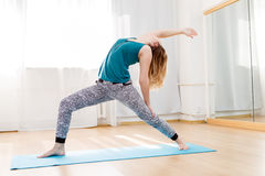 Young woman showing variation of high lunge pose. Yoga exercises in club royalty free stock image