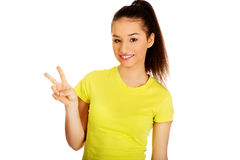 Young woman showing victory sign. Royalty Free Stock Photo