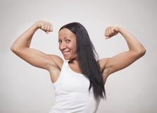 Young woman showing what her arm muscles. On a grey Royalty Free Stock Photo