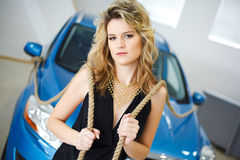 Young woman in the showroom with a new car with ro Royalty Free Stock Image