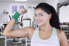 Young woman shows bicep at gym Royalty Free Stock Photos