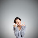 Young woman shows crossed fingers. Isolated on grey Royalty Free Stock Photography