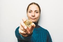 Young woman shows Golden Bitcoin coin - symbol of cryptocurrency, new virtual money, selective focus royalty free stock photo