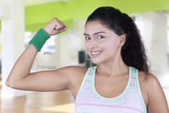 Young woman shows her bicep after workout Royalty Free Stock Image
