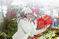 Young woman shows her gift packs inside a Christmas shop royalty free stock images