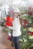 Young woman shows her gift packs inside a Christmas shop Royalty Free Stock Photo