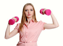 Young woman shows her strengths holding dumbbell. Studio shoot isolated on white Stock Photography