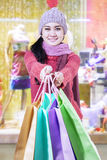 Young woman shows shopping bags Royalty Free Stock Photography