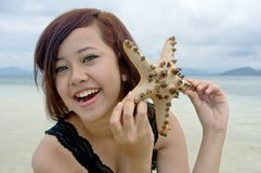 Young woman shows starfish. During holiday at tropical island Royalty Free Stock Photo