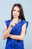Young woman shows threaten fist. Strict beautiful woman shows threaten fist on the blue background stock image