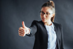Young woman shows thumb up standing on black background, focus on hand. stock photos