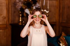 A young woman shows two halves of kiwi indoors. close his eyes. Fruit diet stock photography