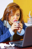 Young woman sick with flu, sitting by table using computer working, looking unwell and tired, medicines, tissues, glass. Of water on desk royalty free stock photo