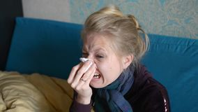 A young woman is sick, sits and wipes her nose with a napkin