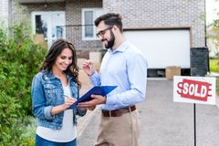 young woman signing contract with realtor while buying stock image