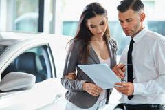 Young Woman Signing Documents at Car Dealership with Salesman.  royalty free stock photos
